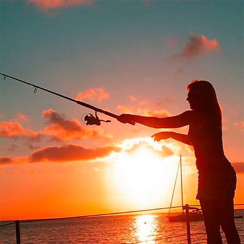 Fishing at sunset - a woman casts a line